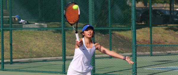 A female player in a white tank top hits the ball.