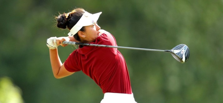 A woman in a red shirt and white visor finishes a golf swing.
