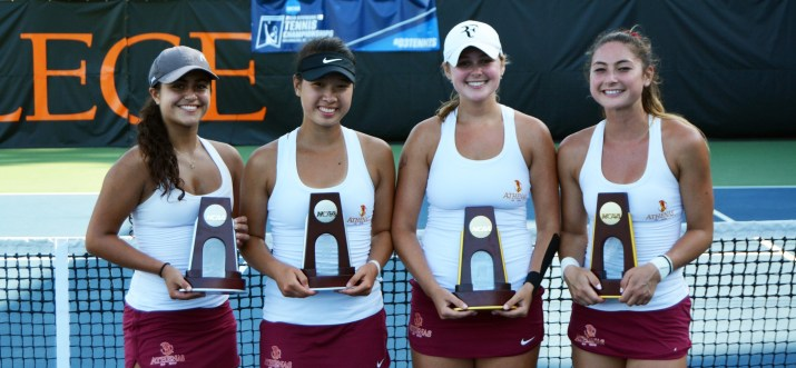 Four women holding trophies stand in front of a net on a tennis court.