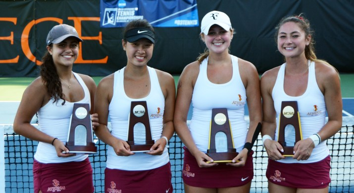 Four women holding trophies stand in front of a net on a tennis court