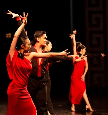 """Dancers on stage, with their arms in raised to form an """"L"""" shape. Nicole Pang SC '20 (left) wears a red dress, while Hans Zhou PO '20 (right) wears a black shirt with red trimming and black pants. Other dancers are in the background."""
