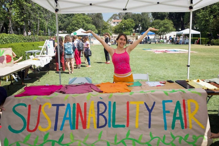 "Sophie Navratil SC '21 poses behind a table with her arms up. She is wearing a pink tank top and orange shorts. On the table in front of her are clothes laid out, and hanging from the table is a colorful sign that says ""Sustainability Fair."""