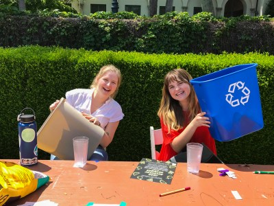 Samantha Bloomfield SC '22 (left) and Mary Iris Allison SC '21 (right) sit behind a brown table at their sustainability booth. Bloomfield is wearing a white t-shirt and holding up a gray trashcan, while Allison is wearing a red shirt and holding up a recycling trashcan.