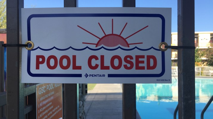 A sign on a fence with a setting sun on it reads Pool Closed. A pool can be seen in the background