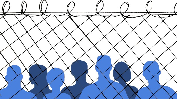 A line of blue silhouettes stand behind a barbed wire fence.