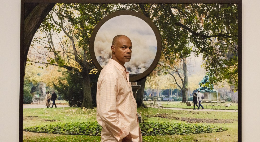 African American male artist Todd Gray stands in front of his piece. The piece combines two photographs, one of a park in Paris and the other of some mountains on fire.