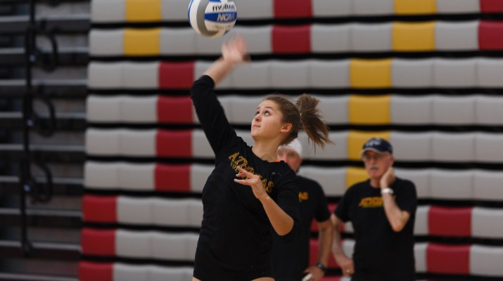 A female college student jumps in the air to serve a volleyball.