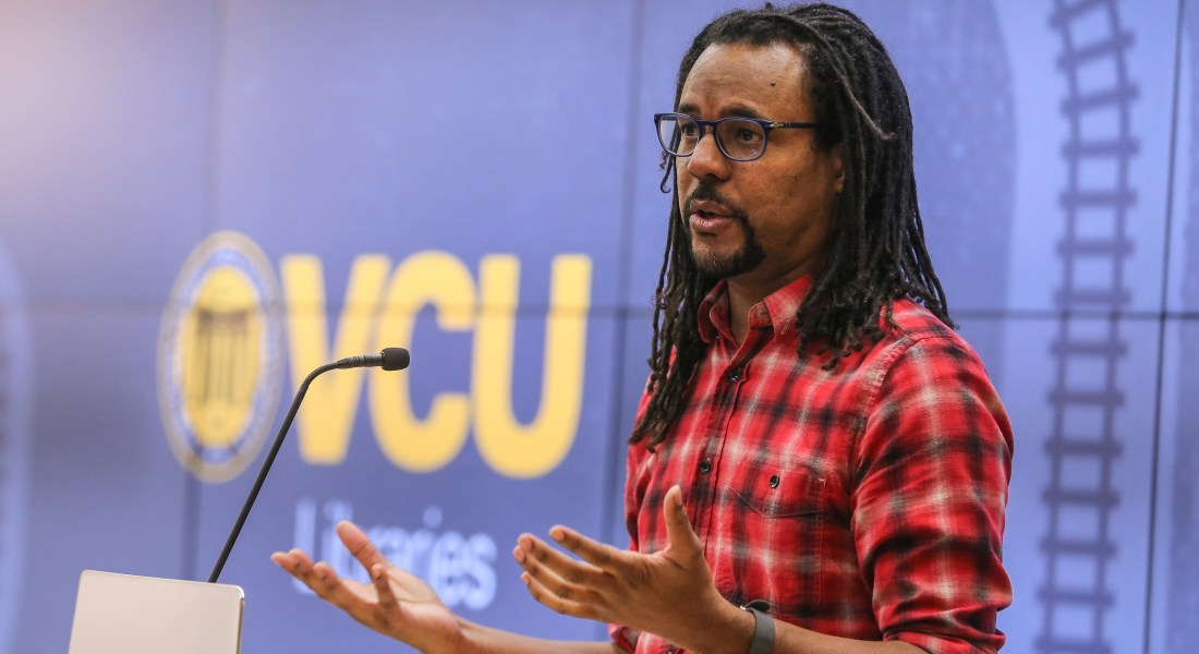 An African American man stands at a podium giving a speech.