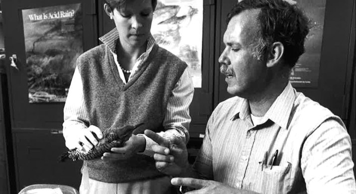 A middle-aged white man, Professor Dan Guthrie, speaks with a younger white female while she holds a taxidermy bird.