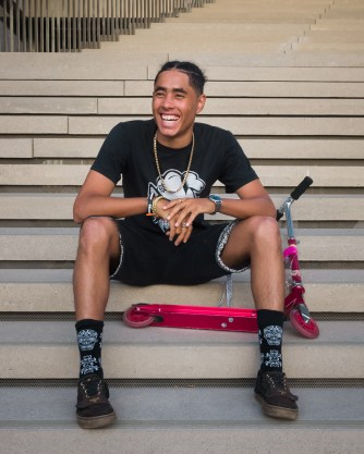 Young student in black and white graphic t-shirt, a chain necklace, black shorts, and black sneakers sits on the steps of an outdoor staircase and smiles. A scooter is beside him, leaned on the steps.