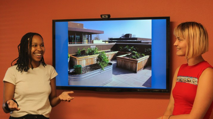 Two female college students stand in front of a tv monitor. It displays an image of a rooftop garden.