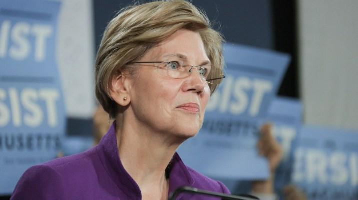 Elizabeth Warren smiling in front of many blue signs