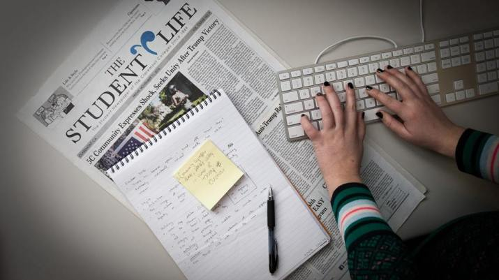 A person types on a keyboard, with a notepad and a newspaper next to the keyboard.