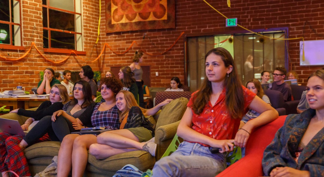Female college students sit on couches in a brick coffeehouse.