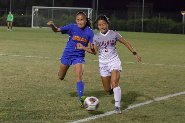Two female college athletes vie for the ball during a nighttime soccer game.