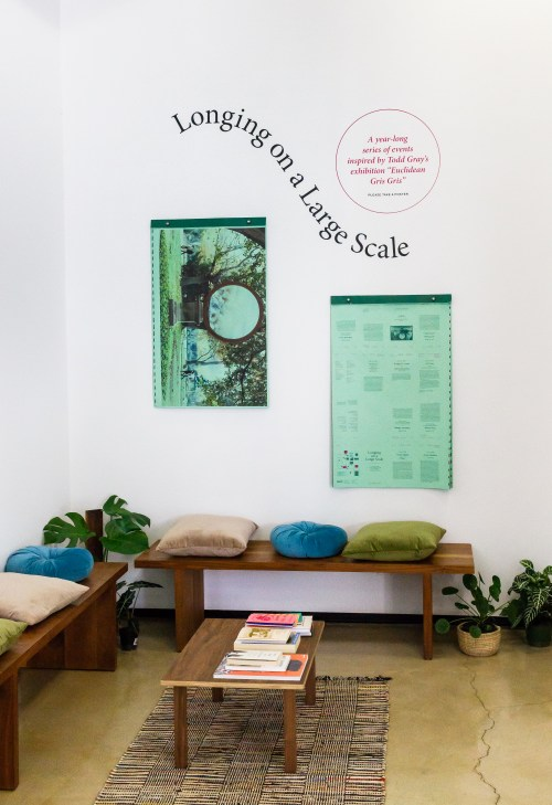 "A museum wall with two rectangular posters and a line of text above that reads ""Longing on a Large Scale."" Two benches are placed in front of the wall, with multicolored pillows on top of them."
