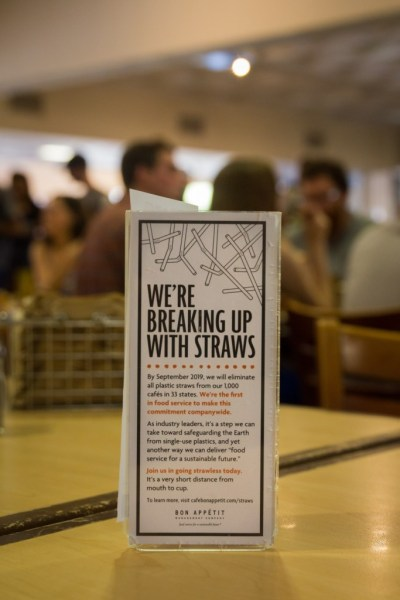 "A Bon Appetit branded sign on a table in McConnell Dining Hall. The sign reads ""We're breaking up with straws. By September 2019, we will eliminate all plastic straws from our 1,000 cafes in 33 states. We're the first in food service to make this commitment companywide. As industry leaders, it's a step we can take toward safeguarding the Earth from single-use plastics, and yet another way we can deliver 'food servie for a sustainable future.' Join us in going strawless today. It's a very short distance from mouth to cup. To learn more, visit cafebonappetit.com/straws."""