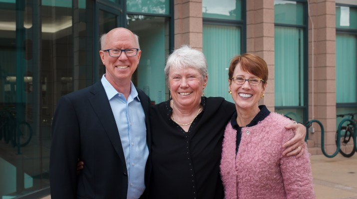 An older woman with white hair wearing black stands in-between a man in a light blue collared shirt and navy blazer and a woman with a pink fluffy jacket and glasses. They smile at the camera and have their arms around each other.