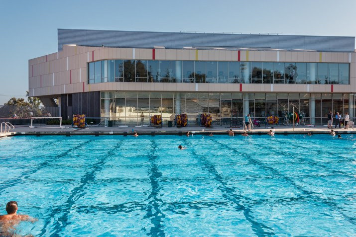 People swim in an olympic-sized pool in front of a modern building.