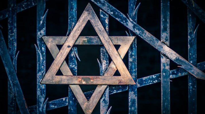 A graphic of a blue iron gate with a wooden Star of David on it.