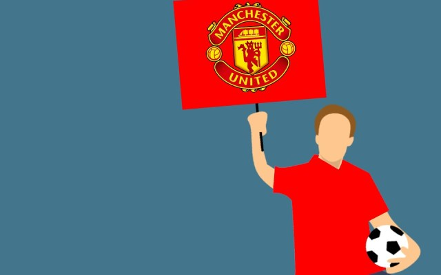A man in a red shirt hold a Manchester United sign and a soccer ball.