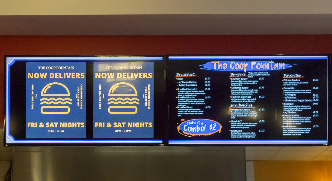 "A TV monitor displays an image the reads ""The Coop Fountain Now Delivers."""