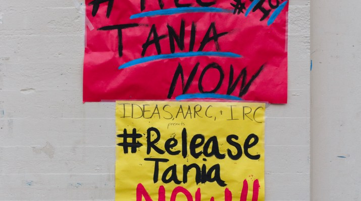 "A pink sign which reads ""#Free Tania Now"" above a yellow sign which reads ""#release Tania now"""