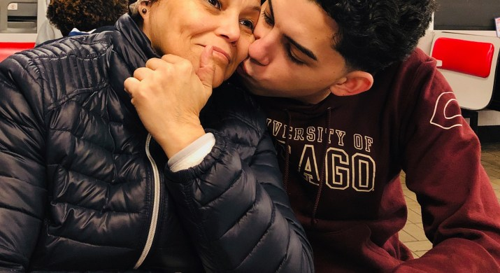 A male college student kisses his mom on the cheek as they sit together.