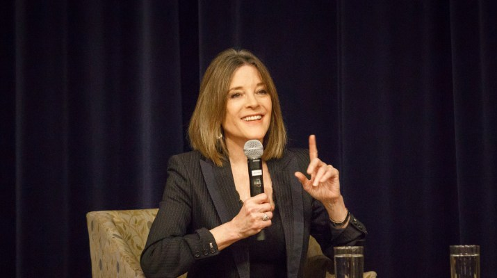 Presidential candidate Marianne Williamson, a 67 year old woman wearing a black blazer, sits on stage speaking into a microphone.