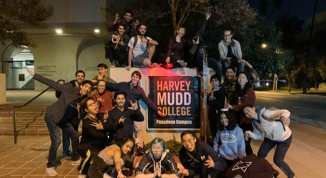"""A group of 20 college students stands around a poster that reads """"Harvey Mudd College Pasadena Campus"""" smiling at the camera."""