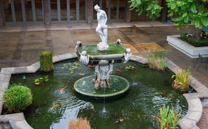A marble fountain with a statue on top containing orange and white koi in a courtyard at Harvey Mudd
