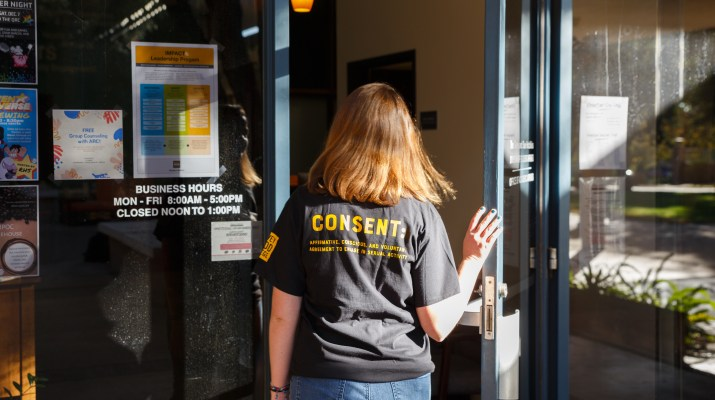 "A woman wearing a black shirt with ""consent"" written on it opens a glass door to walk into an office"