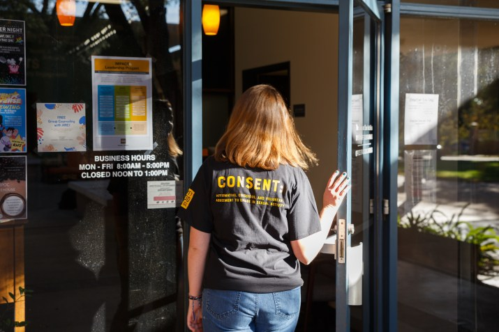 young woman wearing tee shirt with word Consent opening door