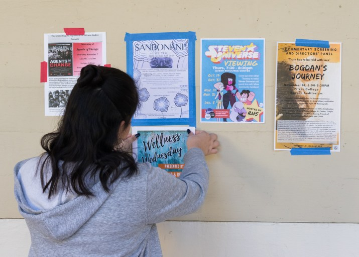 A female college student hangs up a poster on a bulletin board.