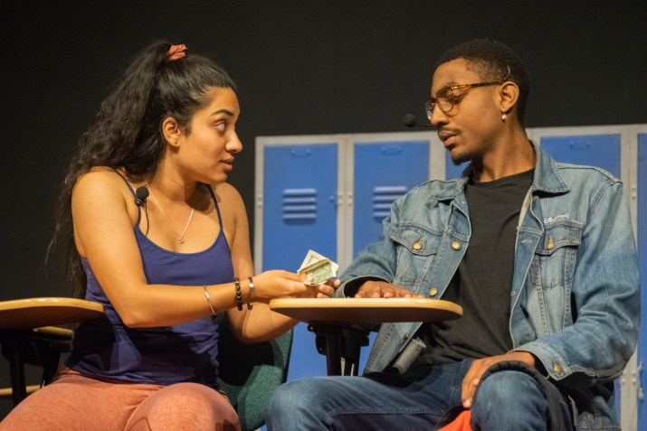 A female student in a purple shirt hands money to a male student in a jean jacket.