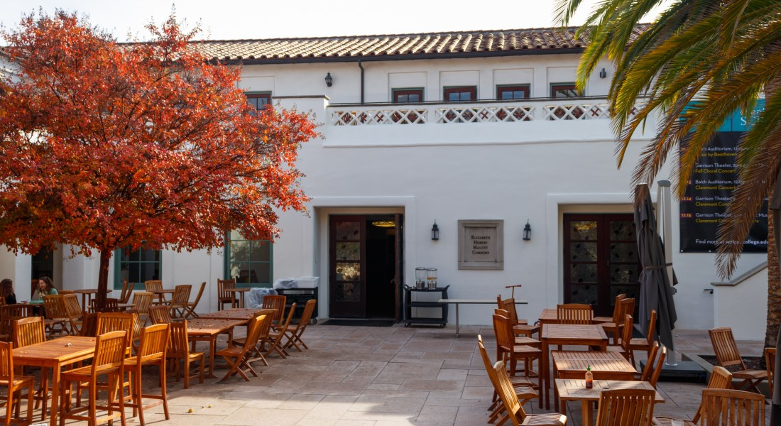 The Scripps College Malott Dining Commons. Wooden chairs and tables are set up outside a white stucco building.