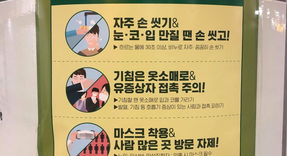 A sign with Korean characters and pictures of washing hands, coughing, and wearing marks