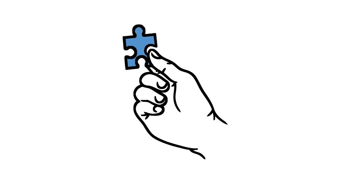 A hand holds up a single puzzle piece.
