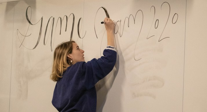 """A blonde girl writes """"Game Jam 2020"""" in cursive on a white board."""