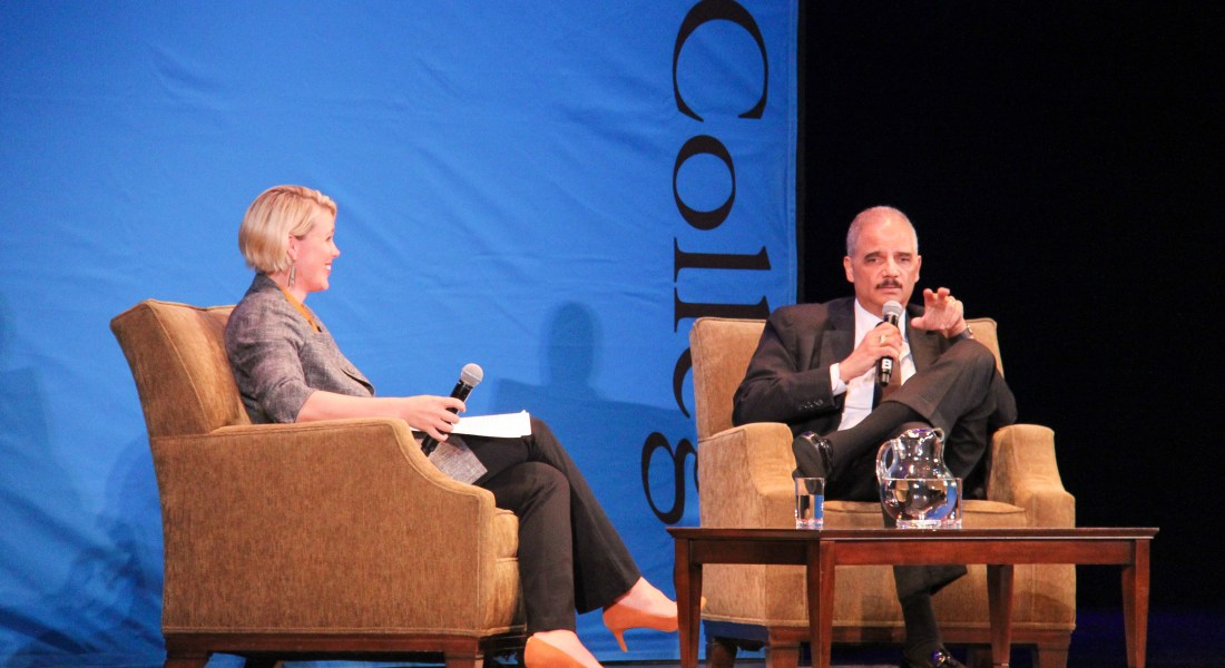 Amanda Hollis-Brusky and Eric Holder sit in armchairs on stage at Bridges Auditorium. Behind them is a blue Pomona College banner, and in front of them is a coffee table with a pitcher of water