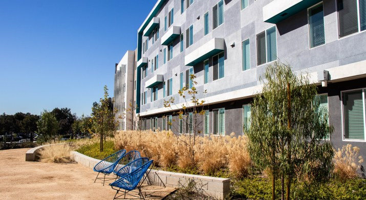 Four blue wire chairs stand in front of a tall, grey apartment building.