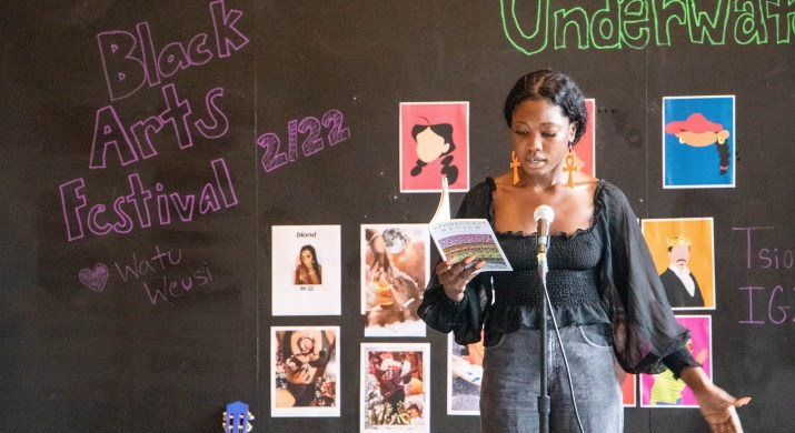 """A woman holding a book speaks into a microphone in front of a chalk board that reads """"Black Arts Festival 2/22"""""""