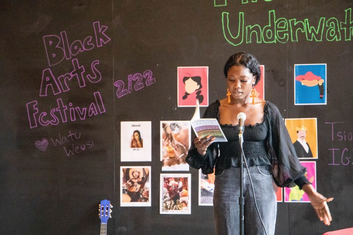 "A woman holding a book speaks into a microphone in front of a chalk board that reads ""Black Arts Festival 2/22"""