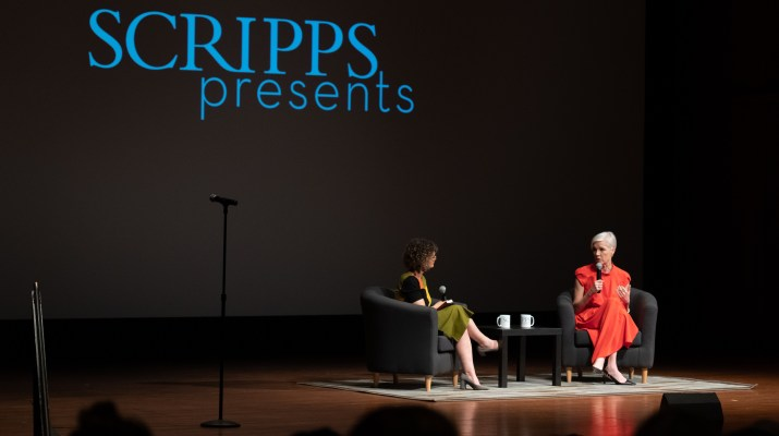 "Two women holding microphones sit in chairs on a stage and talk to a crowd to the right of the image, while ""Scripps Presents"" is displayed on a screen behind them to the left of the image."