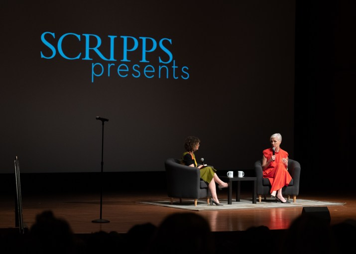 Two women holding microphones sit in chairs on a stage and talk to a crowd to the right of the image, while