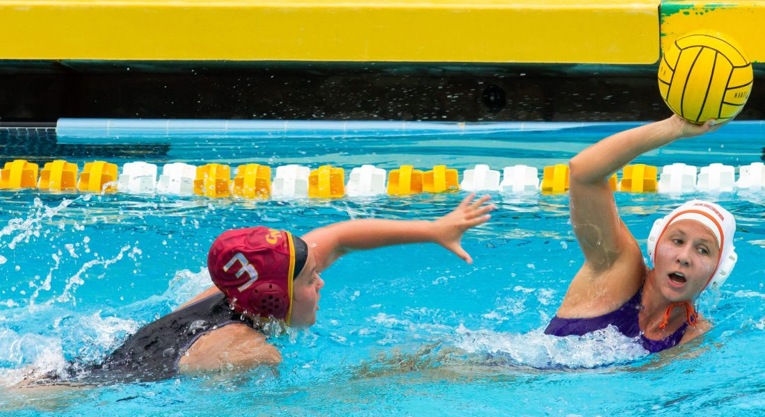 A woman in a pool holds a water polo ball over her head and looks around to pass it to the right of the image, while a second woman stretches out in the water to try and grab the ball.