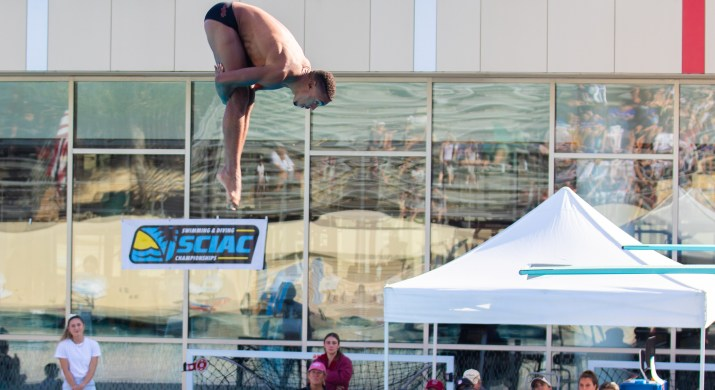 A man has both legs together and grabs around his legs in the air as he dives into a pool.