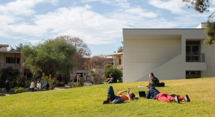 A group of students lounge on the grass next to a building.