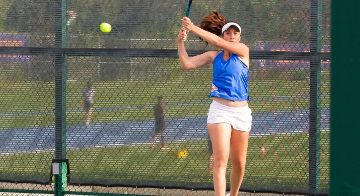 A woman swings a tennis racket over her right shoulder as a tennis ball flies to the left of the image.