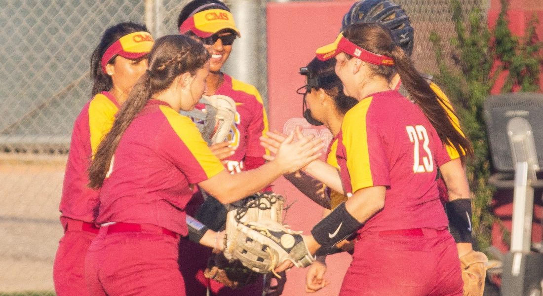 A group of six softball players stand on the pitchers mound, smiling and exchanging high-fives.